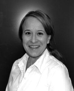 Foto på Anna Sundin. Kvinna med uppsatt mörkt långt hår och vit blus.