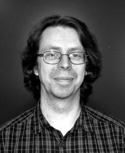 Foto på Lars Östvall. Man i glasögon och rutig skjorta och halvlångt mörkt hår.