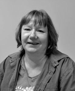 Foto på Monika Lundström. Kvinna med halvlångt, halvblont hår, skjorta och t-shirt.