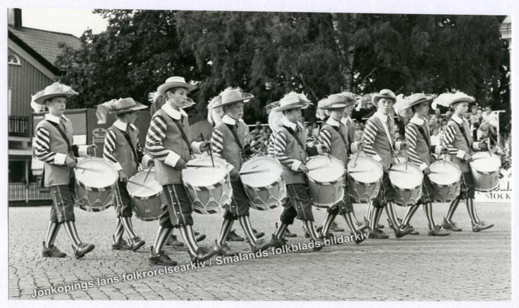 Marscherande utklädda pojkar som spelar på marschtrummor. I bakgrunden skymtas en grupp åskådare.