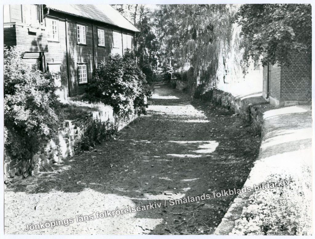 Jordväg omgärdad av stenmur, växtlighet och bebyggelse.