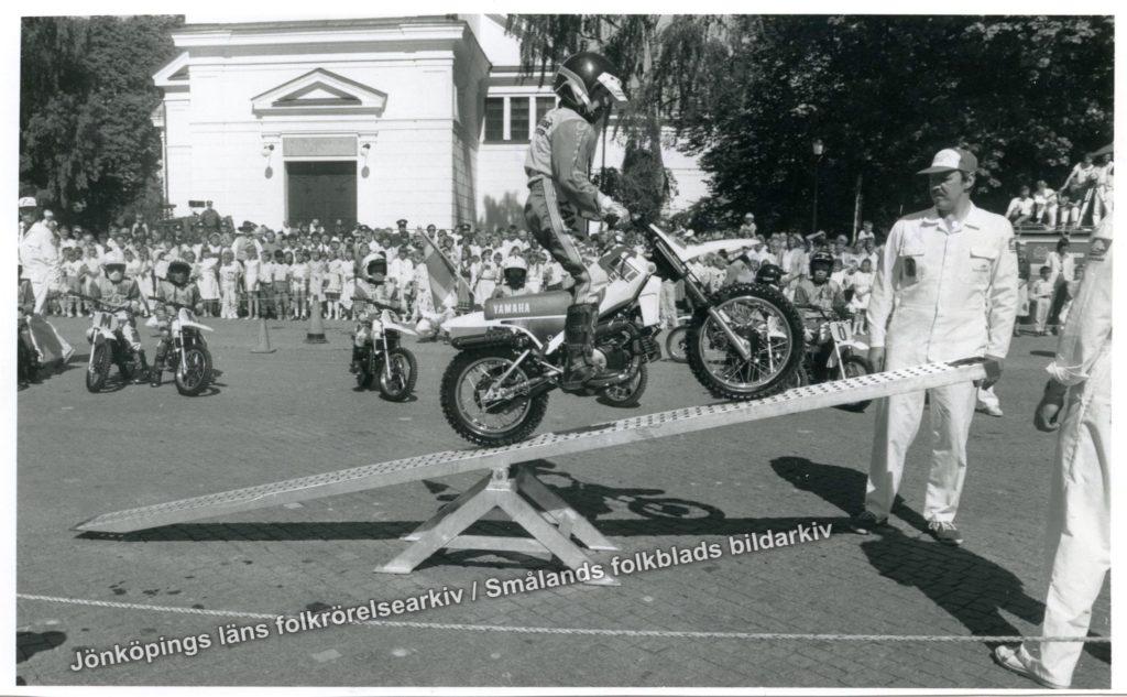 En motocrossförare i full mundering åker upp på en vippbräda som står på ett torg. I bakgrunden en stor samlingen människor.