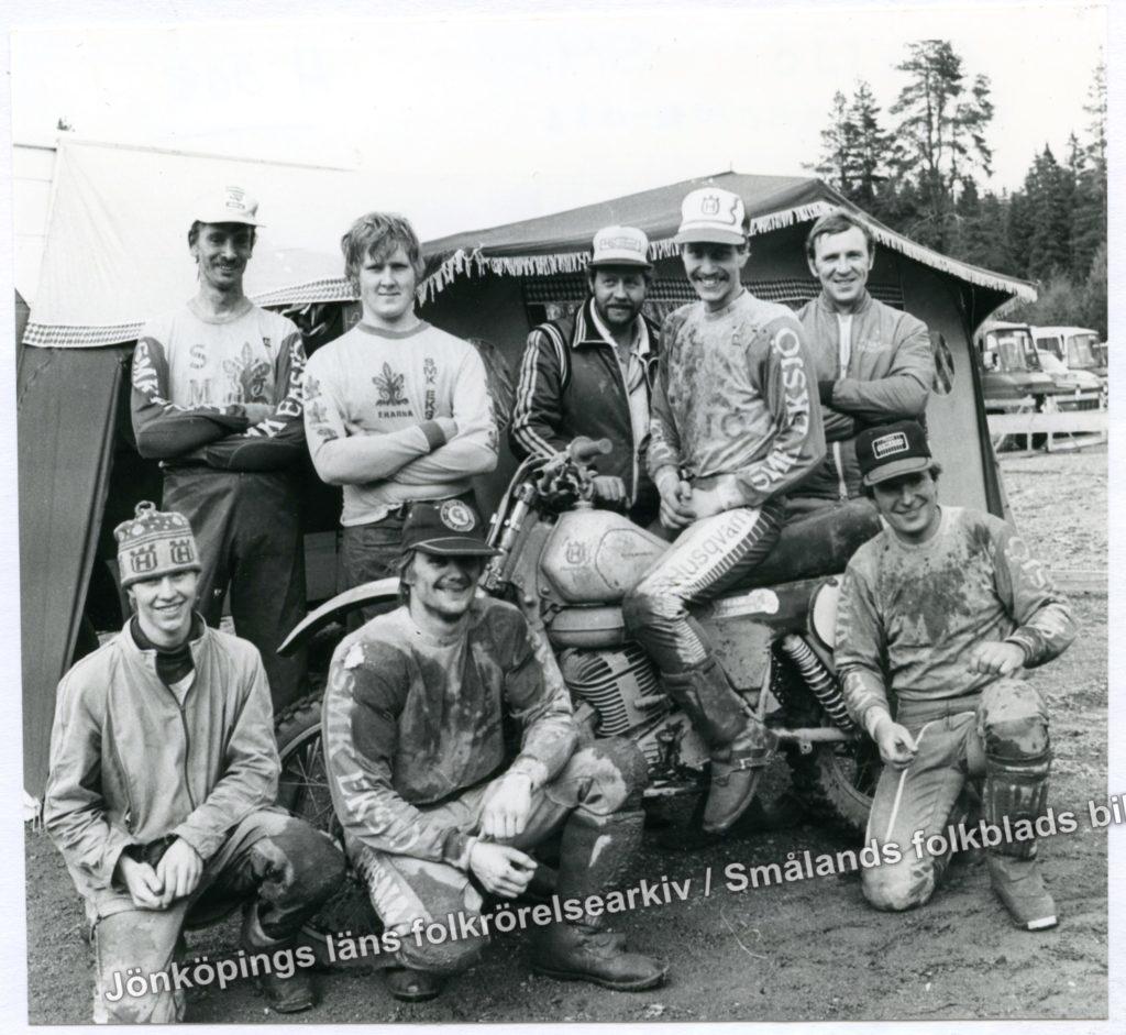 Nio stycken män klädda i leriga motocrosskläder framför ett tält. Fyra av dem står, tre sitter på knä och en sitter på en motocross i mitten av samlingen.