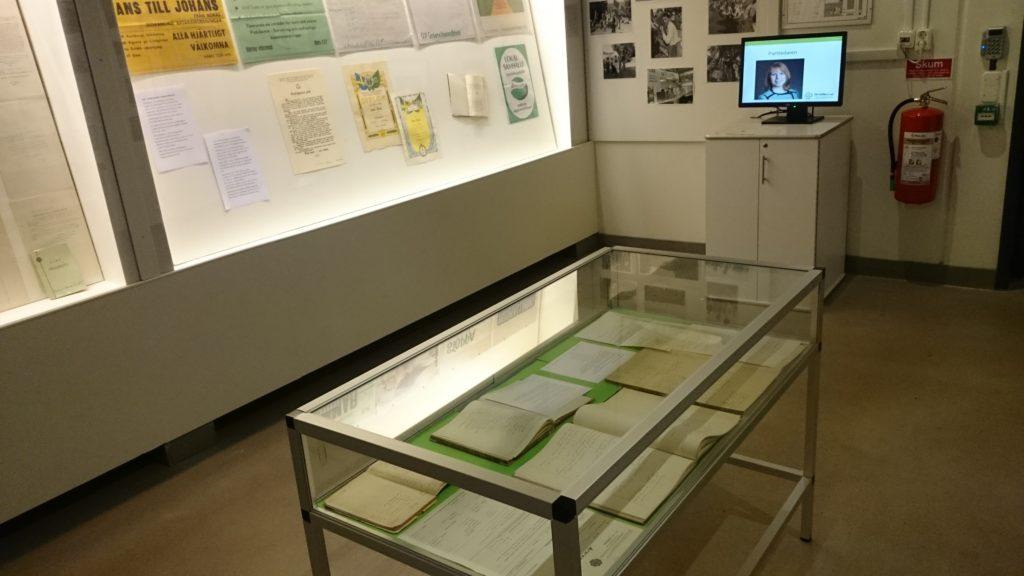 Dokument och protokollböcker i monter. I bakgrunden en datorskärm som visar ett bildspel.