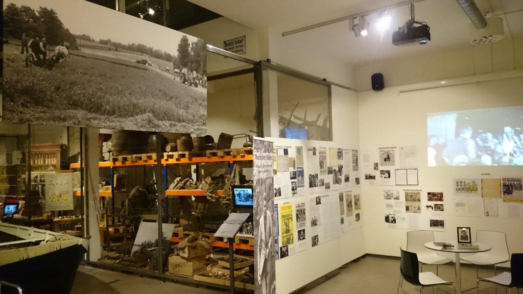 Fotografier och affischer monterade på vägg. Ett stort foto monterat på balk nära tak.