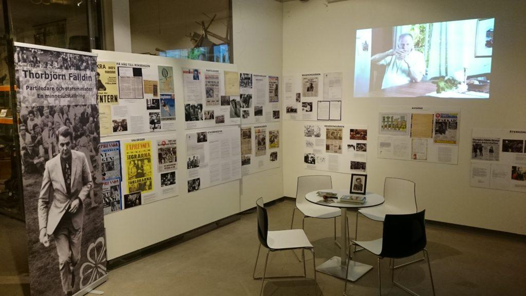 Fotografier och affischer monterade på vägg. En film projiceras på vägg.