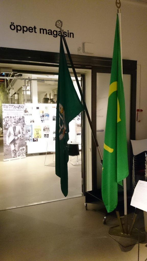 Två gröna fanor hänger i öppningen till utställnigslokal.