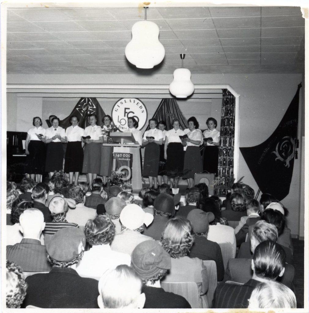 Ett femtontal kvinnor i kjol och blus står på en scen och sjunger. I bakgrunden hänger fanor. Nedanför scenen sittande publik.