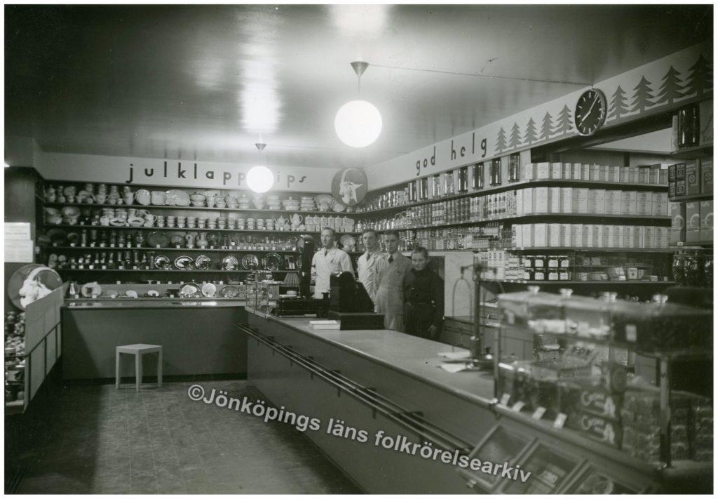 Fyra personer bakom en lång disk inne i en butik. Väggarna är täckta av varor.
