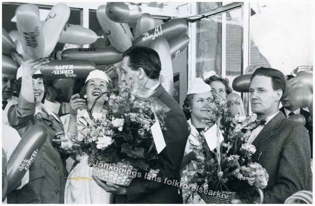 Män och kvinnor håller i blomkorgar. I bakgrunden ballonger.