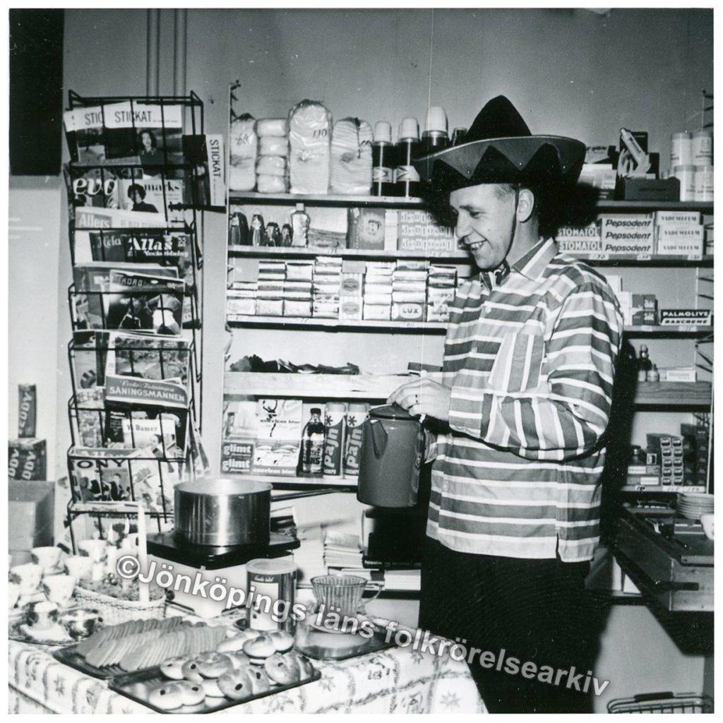 Man i sombreroliknande hatt häller upp kaffe i en butik.