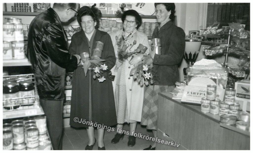 Tre kvinnor tar emot blommor och kaffeburkar av en man inne i en butik.