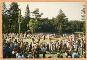 En stor samling människor på ett fält. I mitten en midsommarstång.