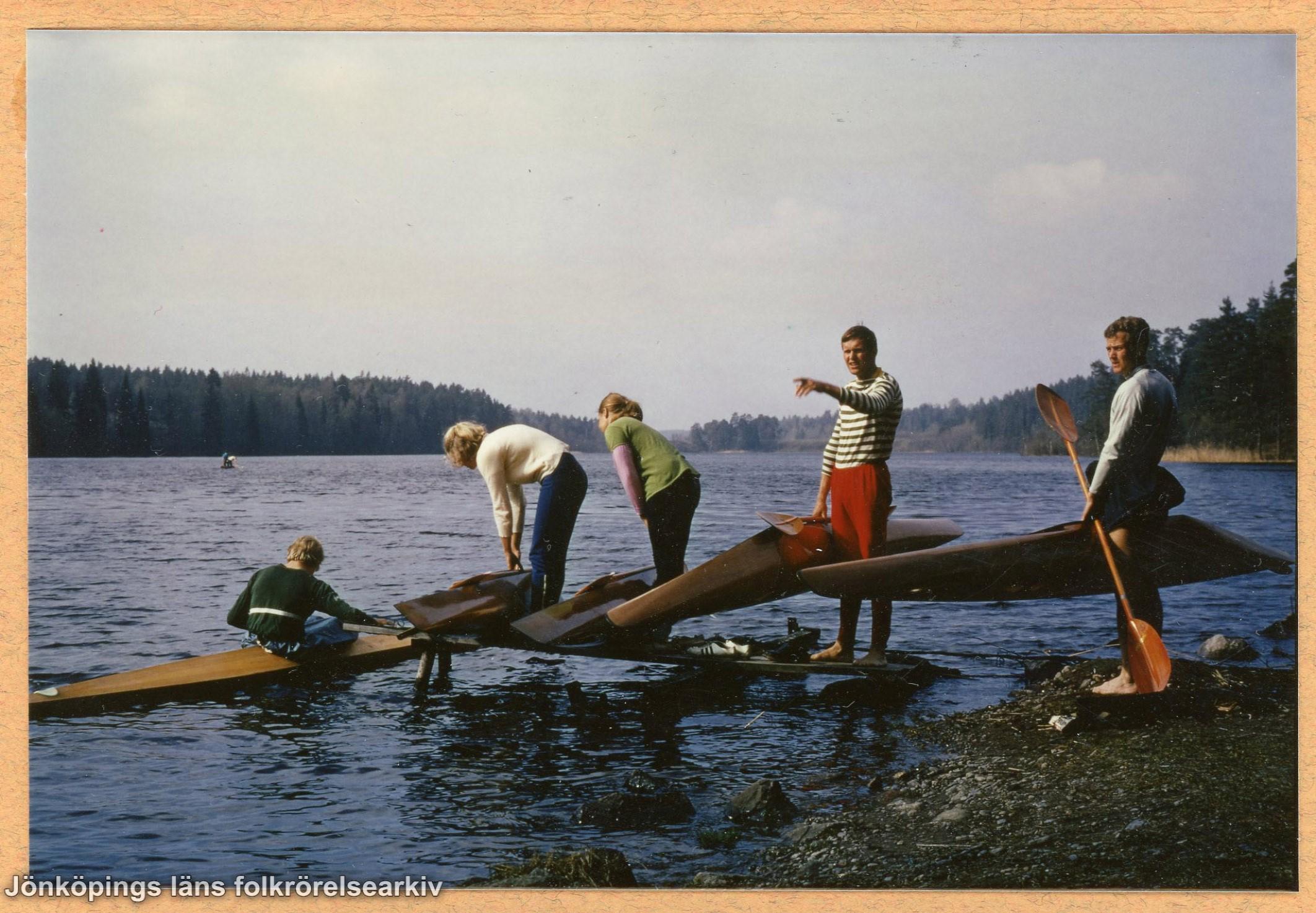 Fem människor sjösätter några kanoter.