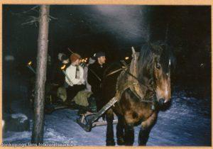 Människor åker häst och släde. I händerna har de ljus.