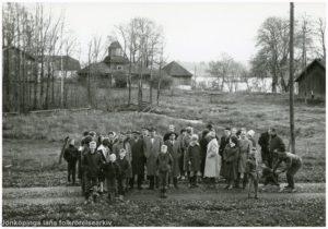 En grupp människor på en grusväg. I bakgrunden en stor träbyggnad. Längre bort skymtar en sjö.