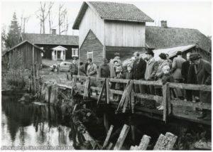 En grupp människor på en träbro. I bakgrunden gamla trähus.