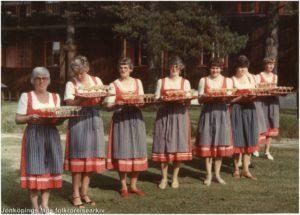Sju kvinnor i någon slags landskapsdräkt står uppställda med brickor i händerna.