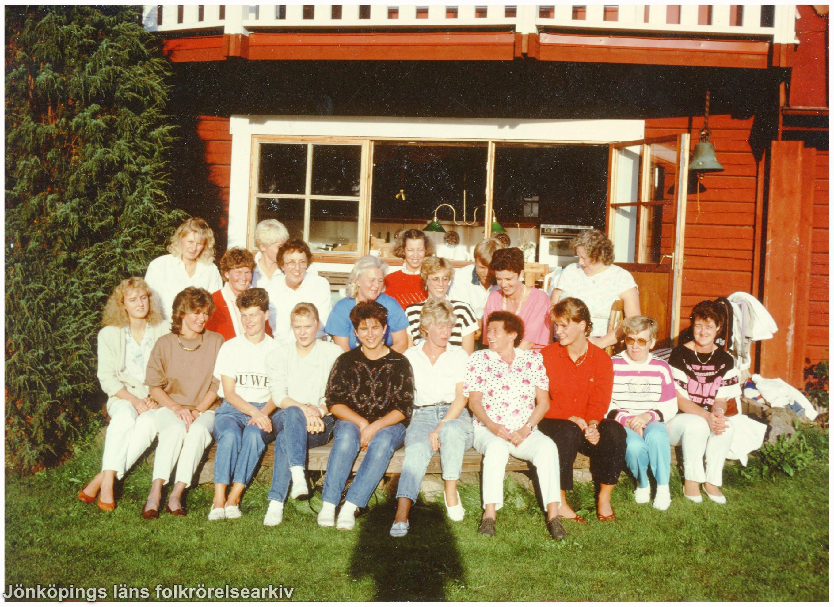 Ett tjugotal människor sitter vid en röd stuga.
