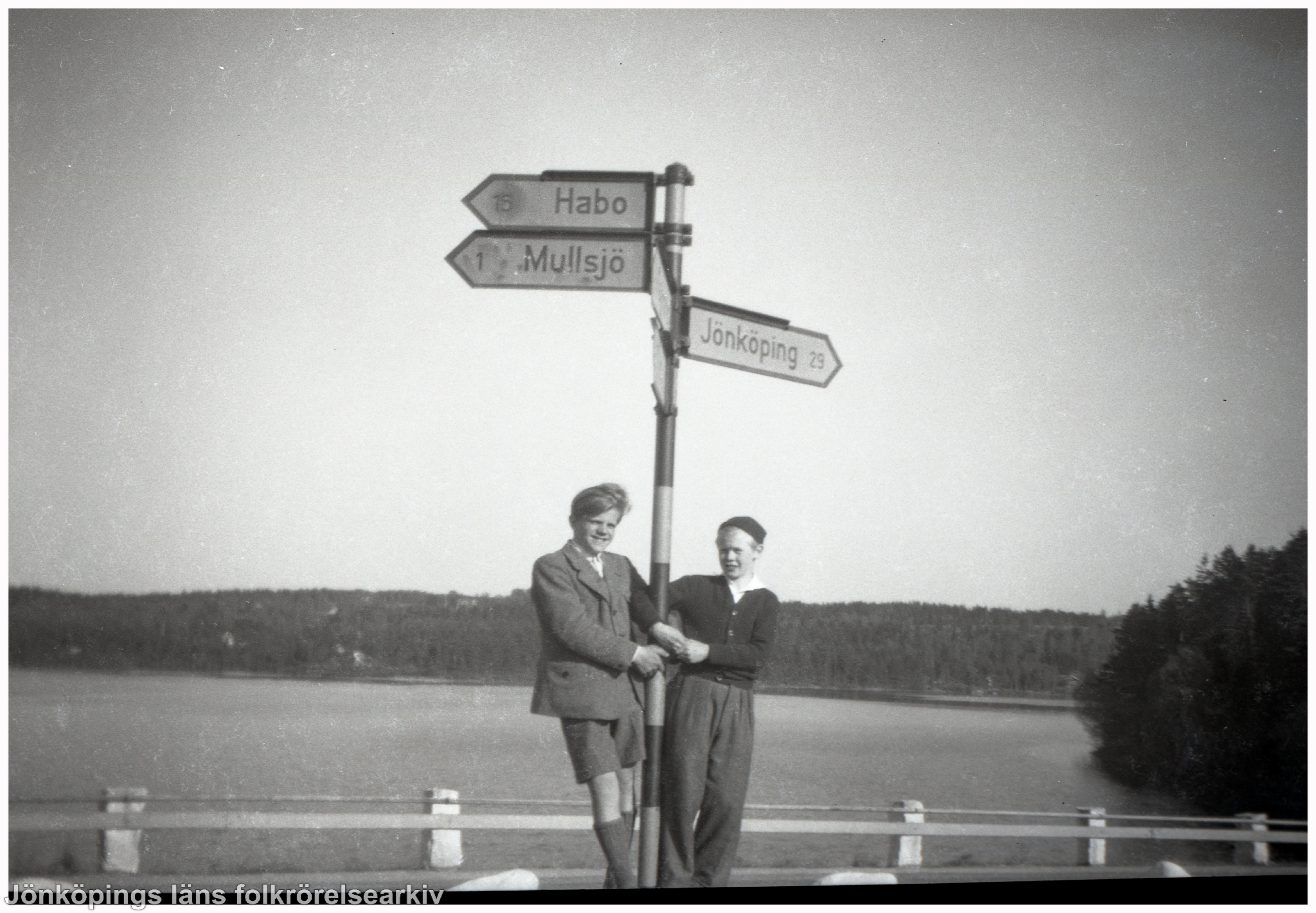 Två pojkar står vid en stolpe med tre skyltar Habo, Mullsjö, Jönköping.