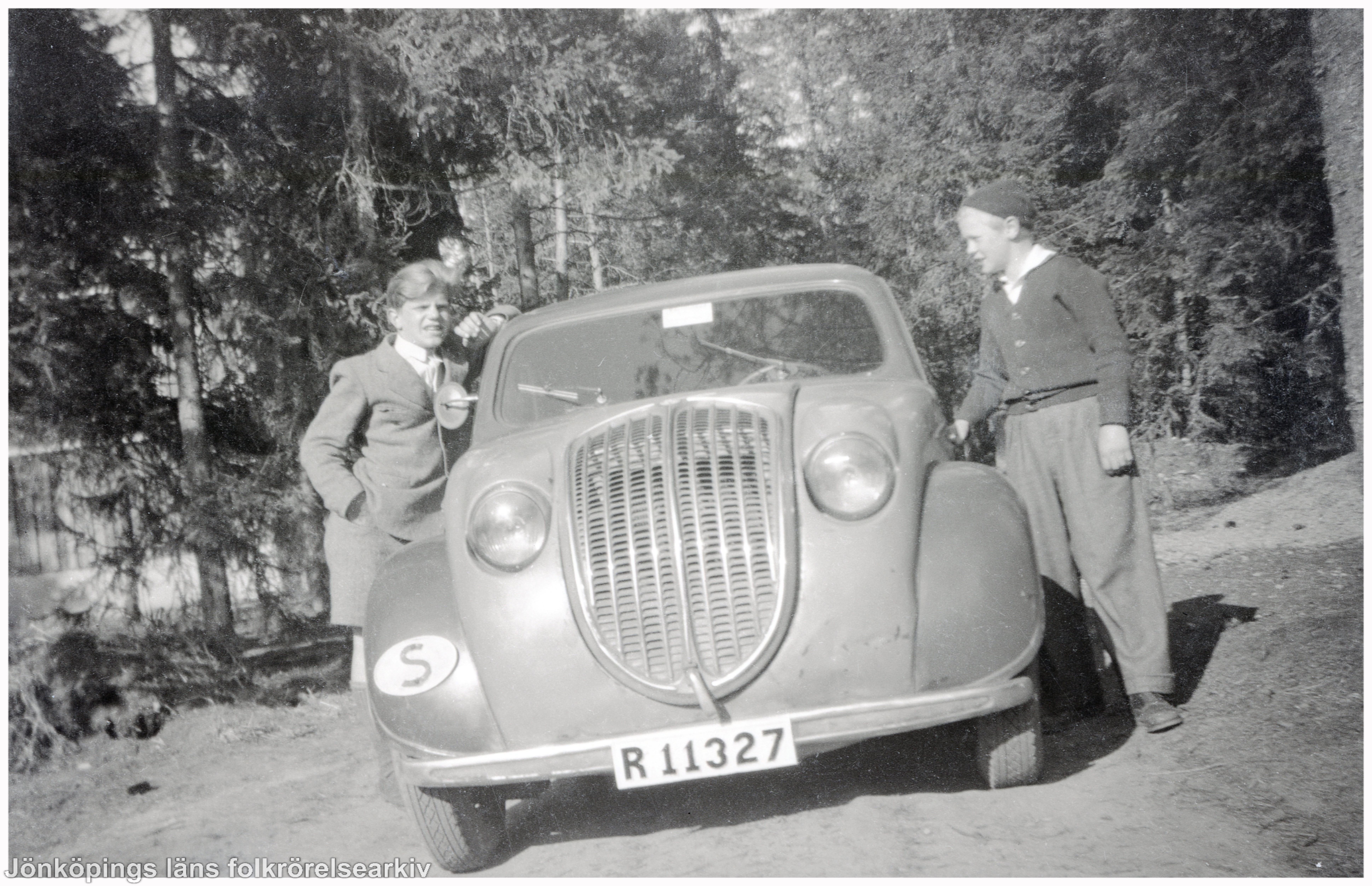 Två pojkar står på varsin sida av en bil.