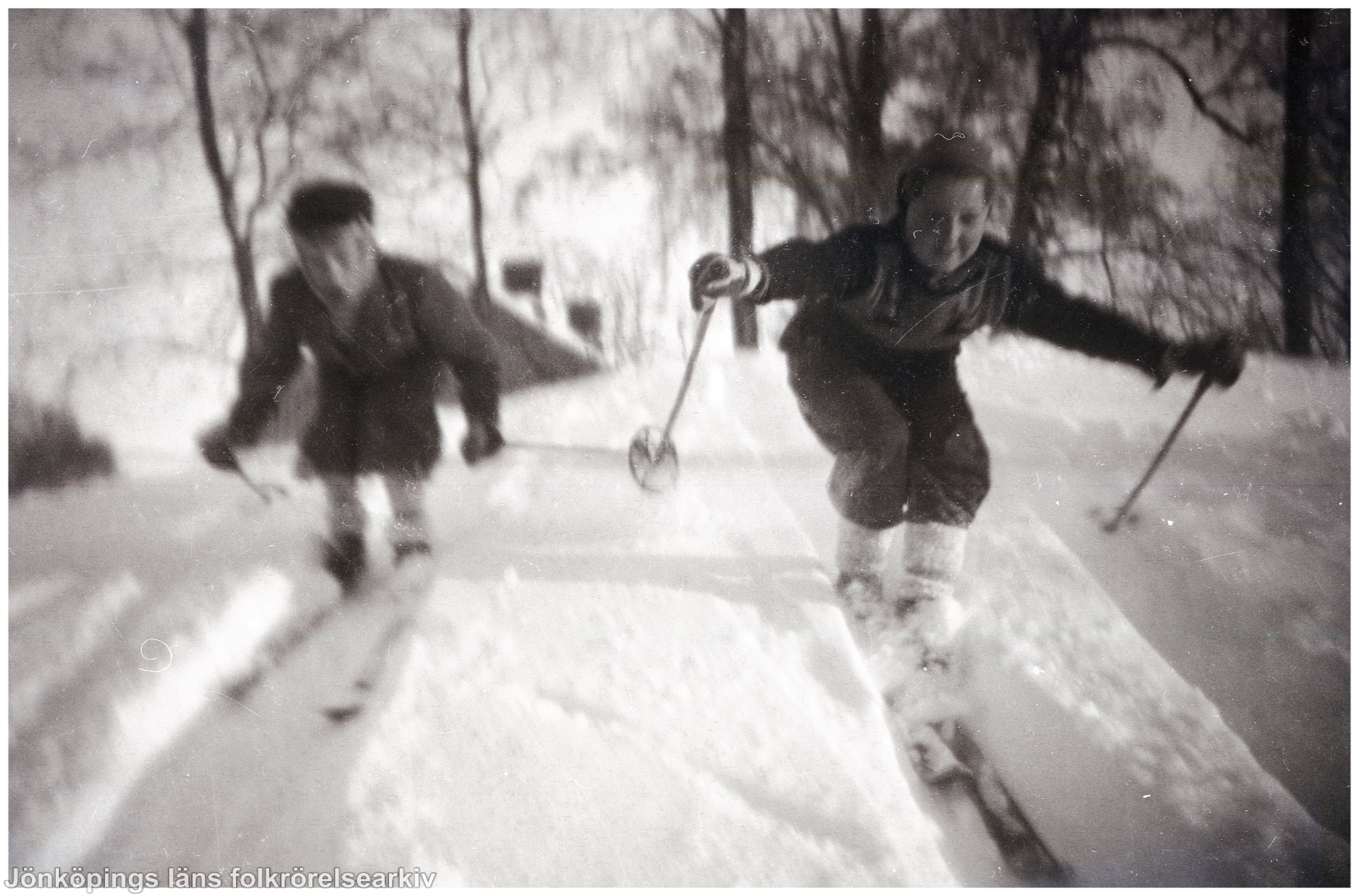 Två barn åker skidor nerför backe.
