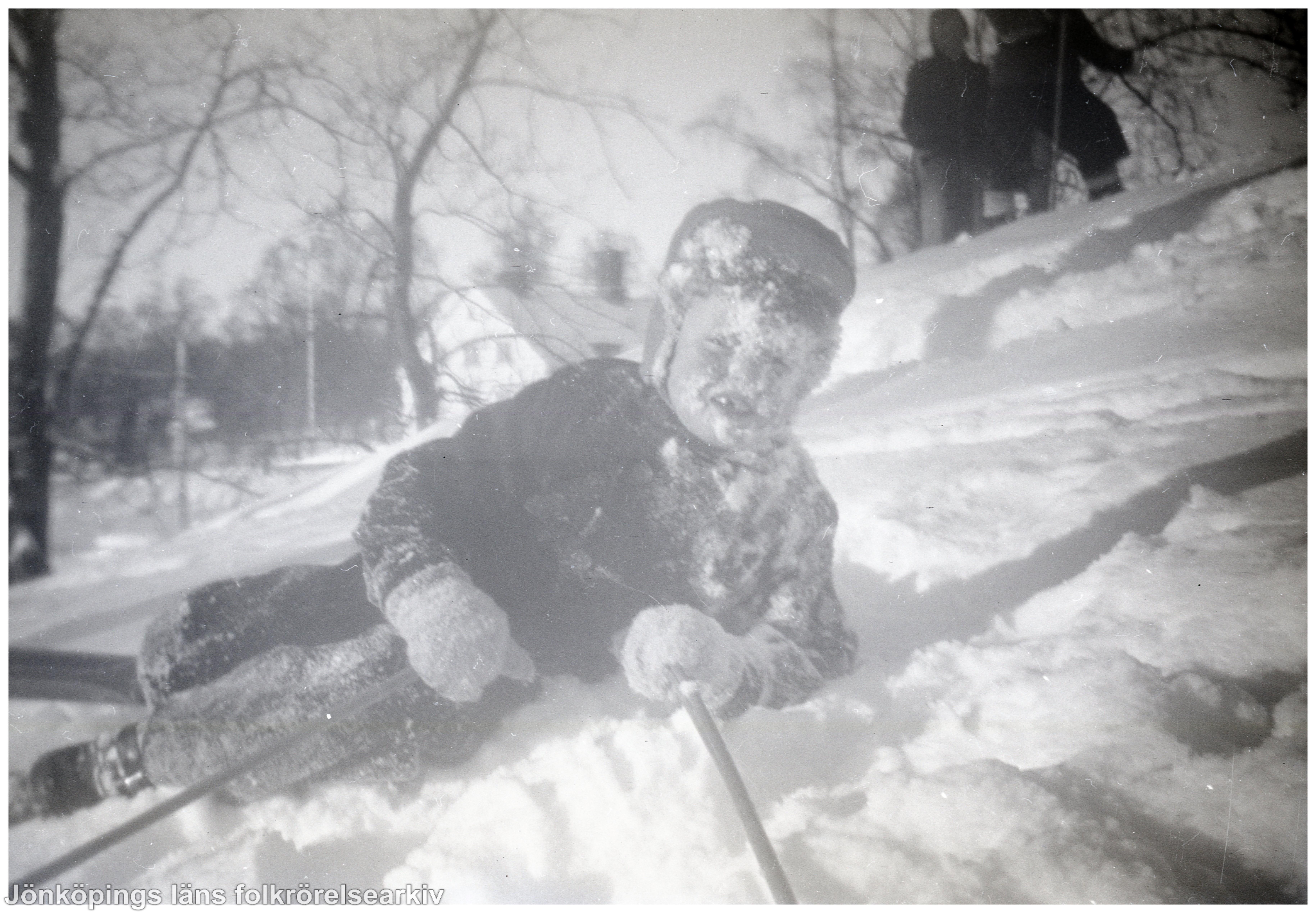 Ett barn i skidutrustning ligger i en backe. Han har snö i ansiktet.