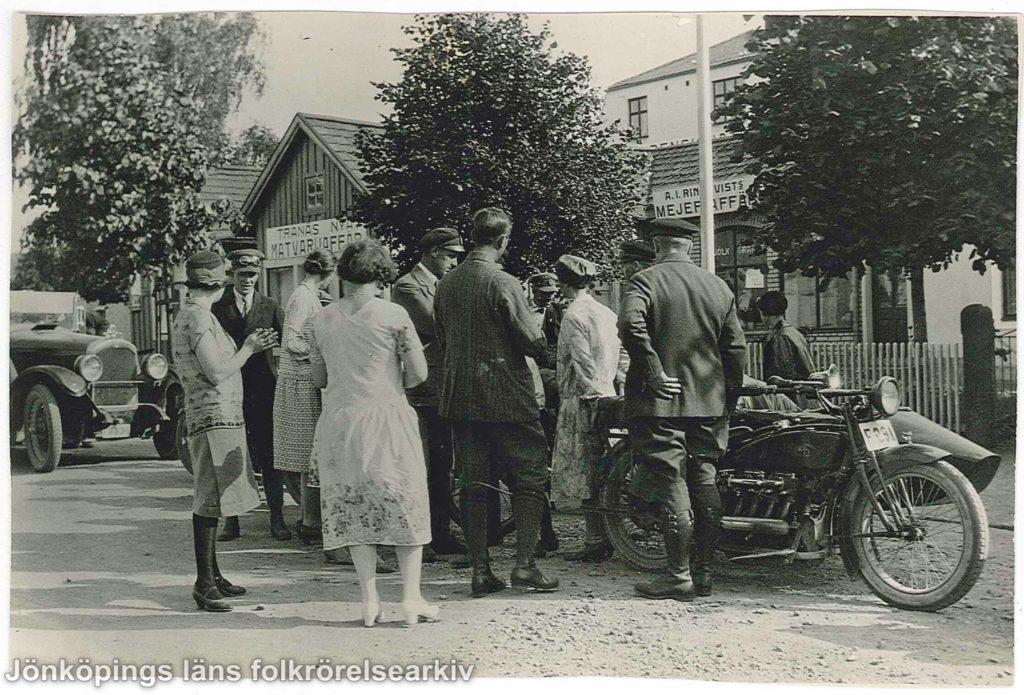 Ett tiotal män och kvinnor samlade runt en motorcykel med sidovagn. I bakgrunden en bil och ett trähus med en skylt som det står Tranås nya matvaruaffär på.