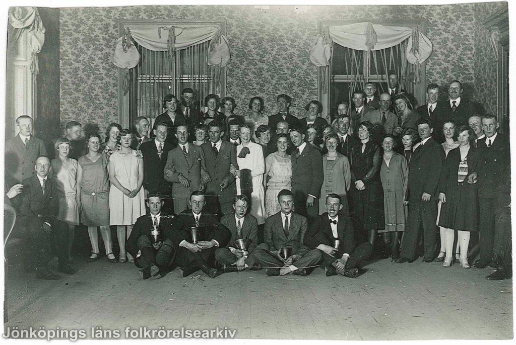 Ett fyrtiotal personer, både män och kvinnor, uppställda för fotografering i en samlingslokal. Längst fram sitter fem män på golvet med benen i kors. I händerna håller de någon slags pokal.