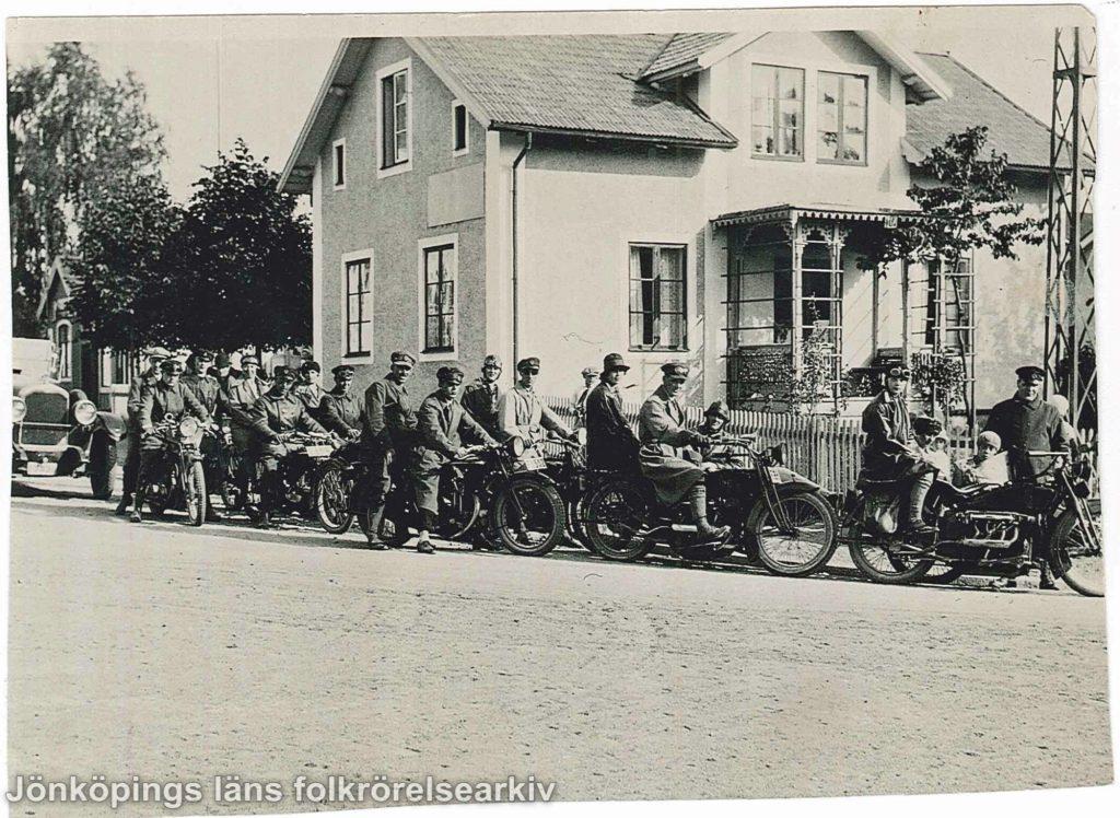 Ett tjugotal personer på motorcyklar framför ett putsat stenhus. En del av motorcyklarna har sidovagnar i vilka barn sitter.