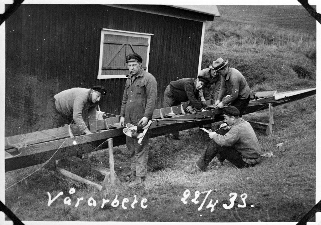 6 män i hattar och mössor och arbetskläder arbetar med en kanot som ligger på en ställning. Några meter bakom kanoten ser man en del av ett träshus med stängda träluckor för fönstret. En av männen har en pipa i munnen och tittar in i kameran.