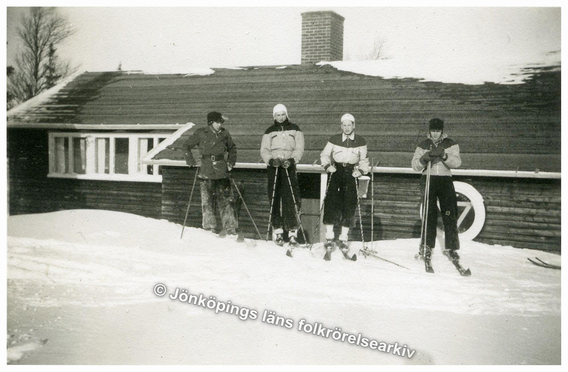 Fyra stycken unga män i skidutrustning framför en trästuga.