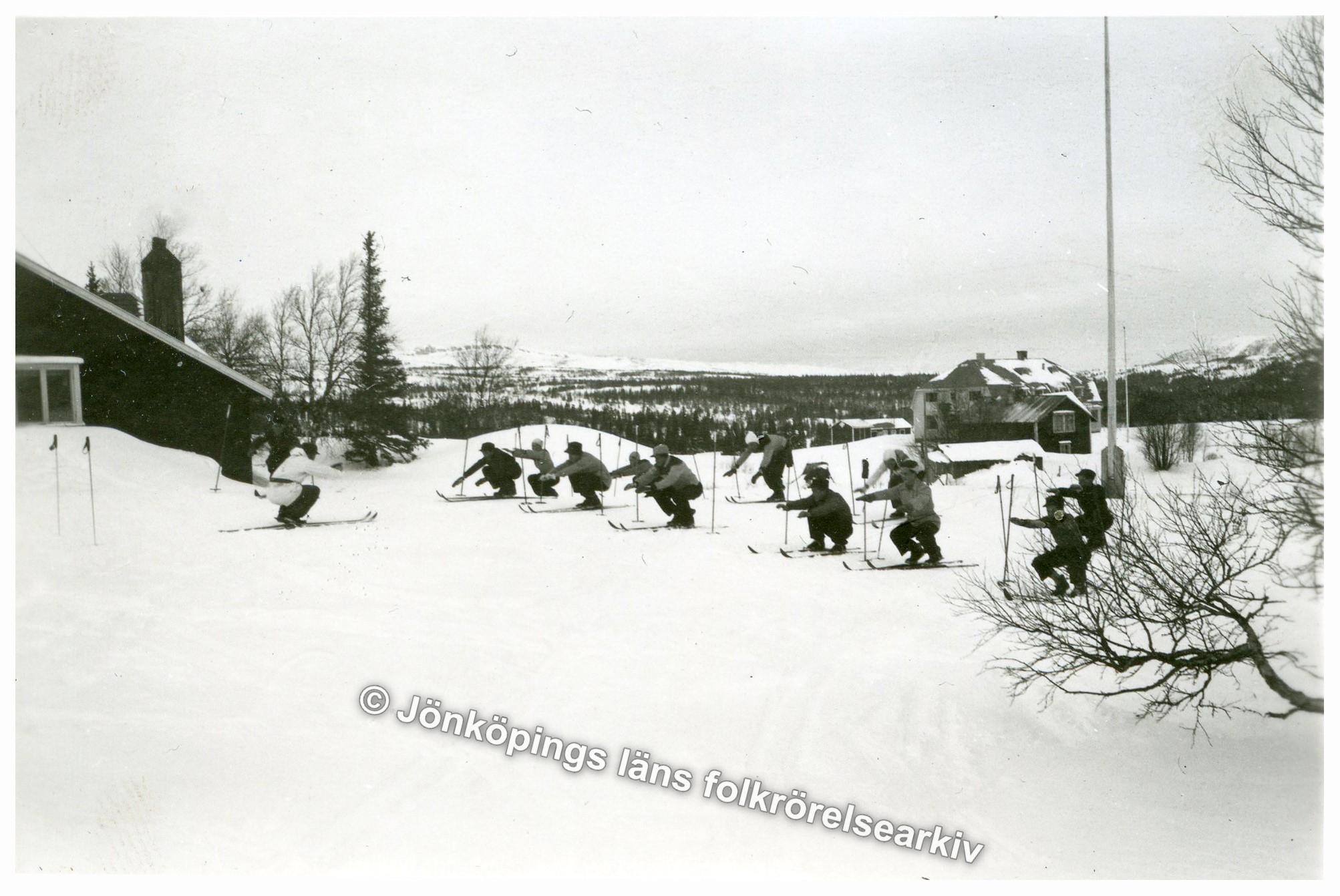 En grupp ungdomar utför någon slags gymnastisk uppvärmning med skidor.