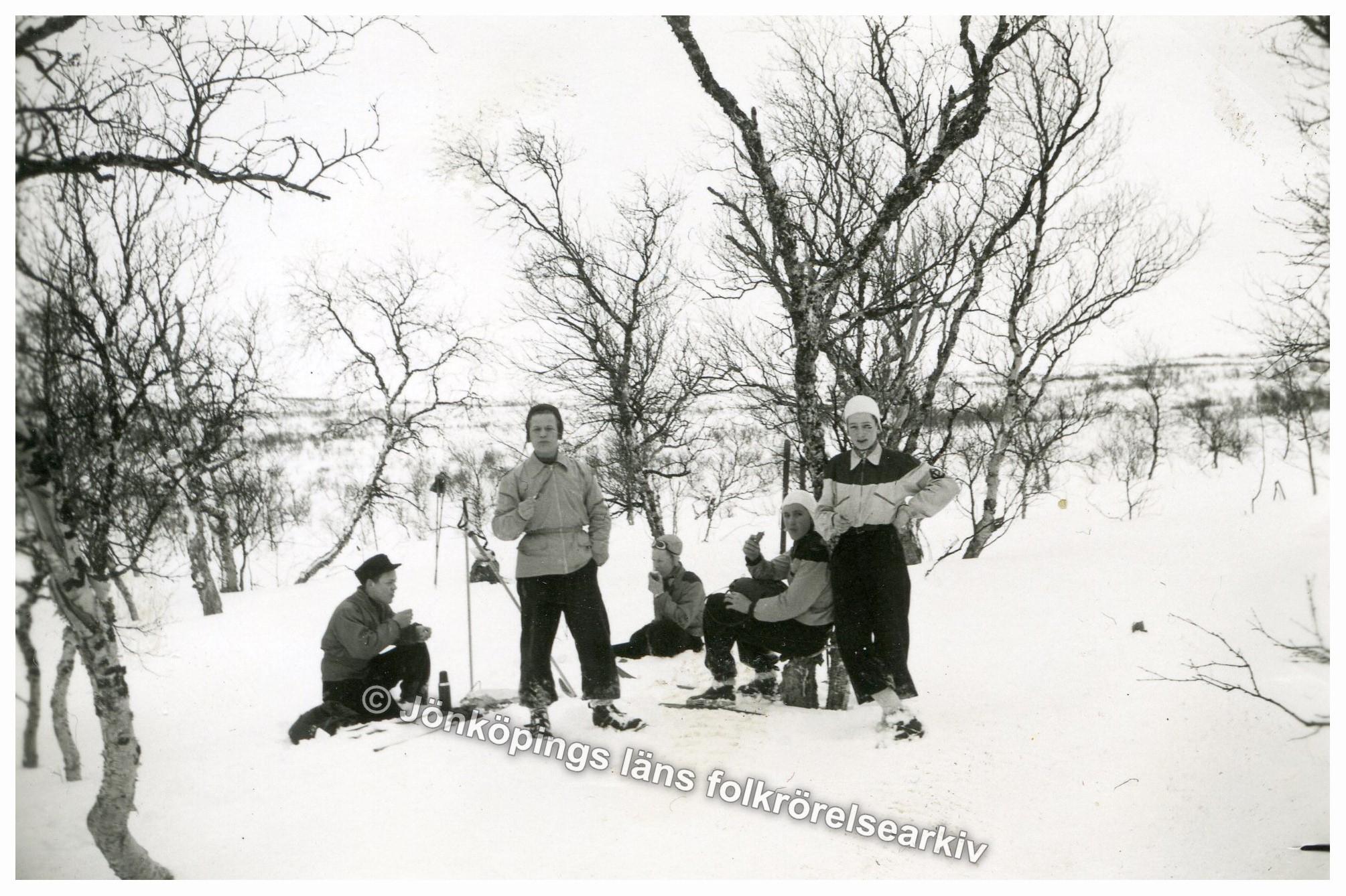 Fem ungdomar sitter eller står och intar en matsäck i snön.