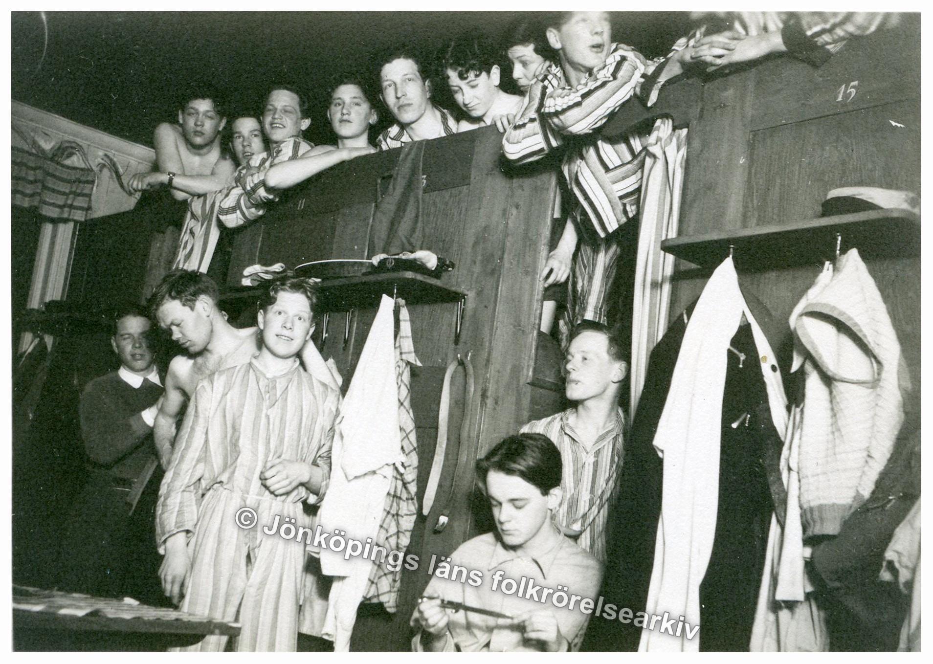 En grupp ungdomar i pyjamas trängs i ett rum.