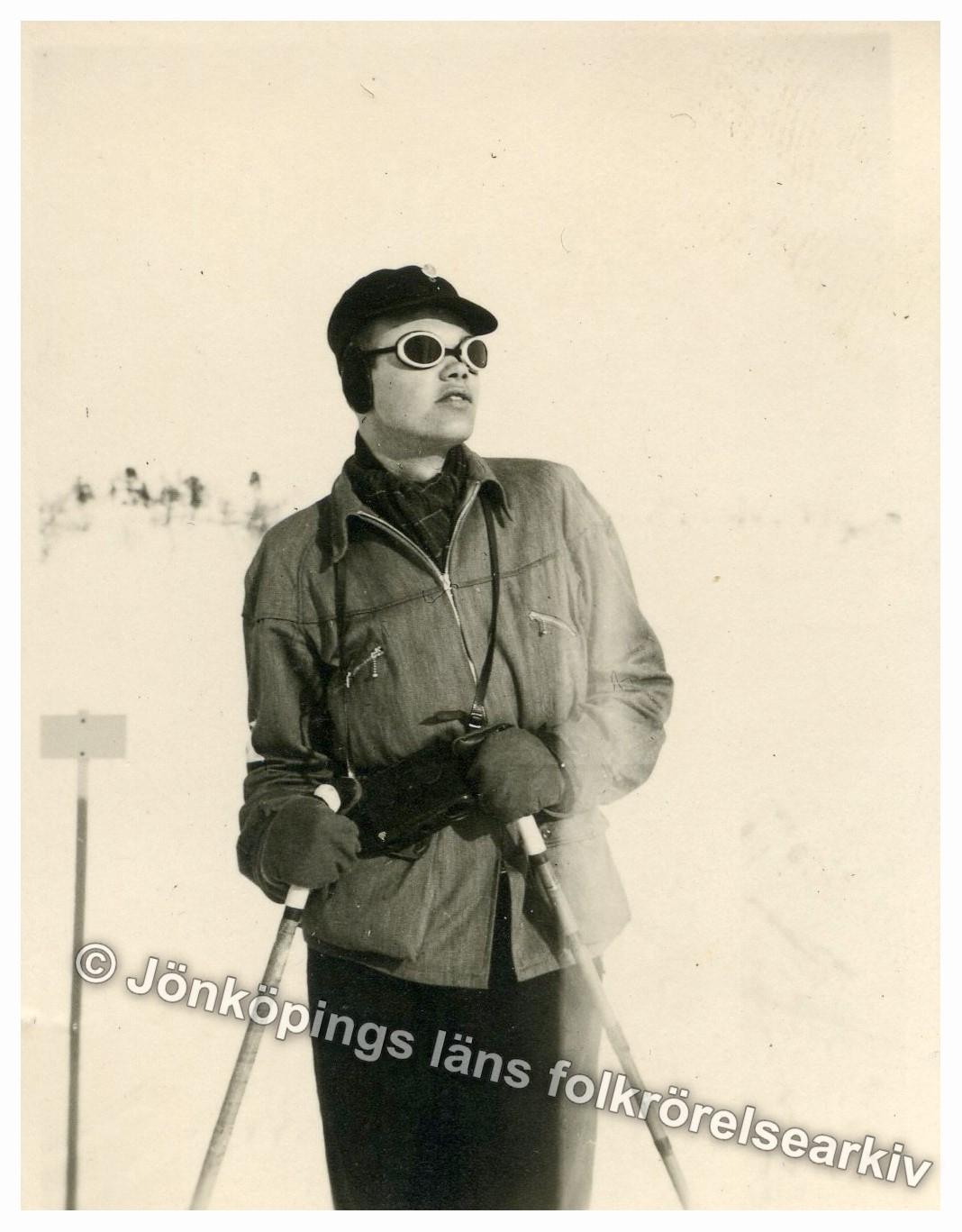 Ung man i vinterkläder och solglasögon poserar för kameran. I händerna håller han ett par stavar.