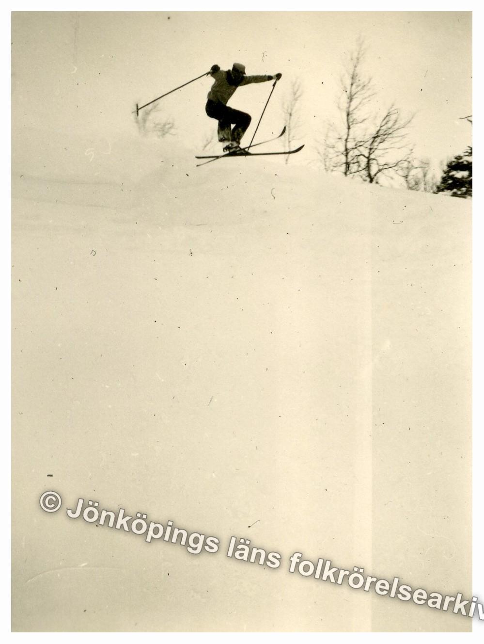Vinterklädd person gör ett hopp med skidor i en backe.