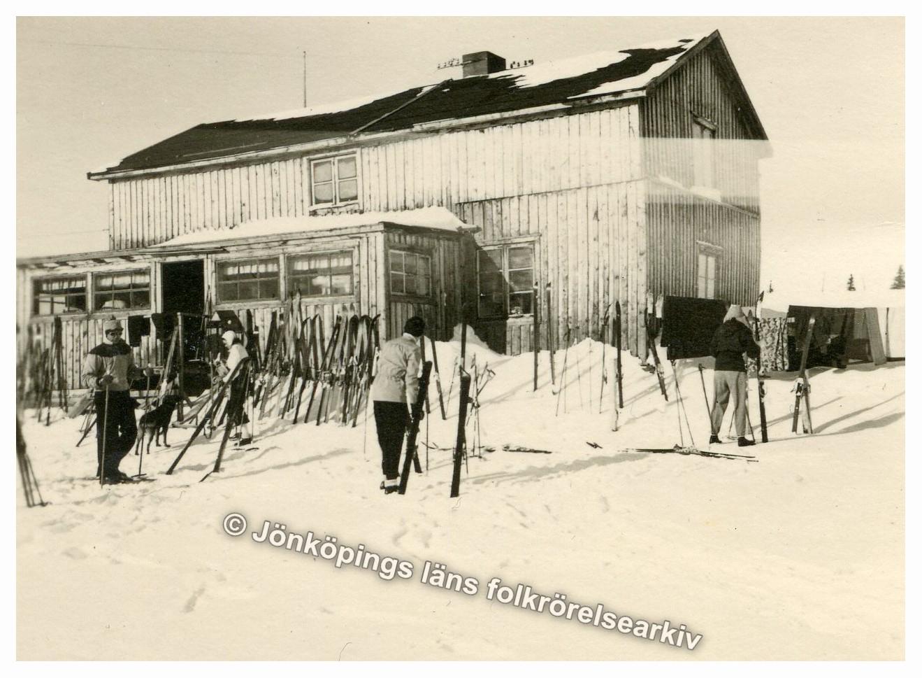 Fyra personer tar av sig skidutrustning utanför en stuga. Ett stort antal skidor och stavar är nedstuckna i snön.