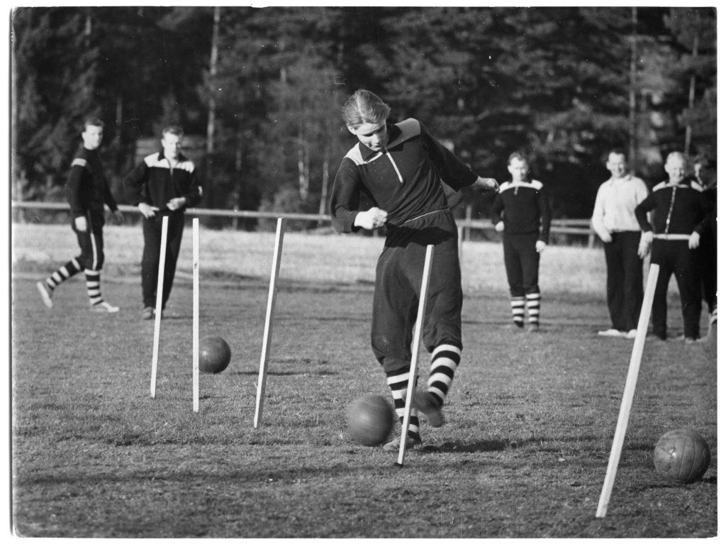 Fotbollsträning. En spelare springer slalomdribblar genom käppar med bollen.
