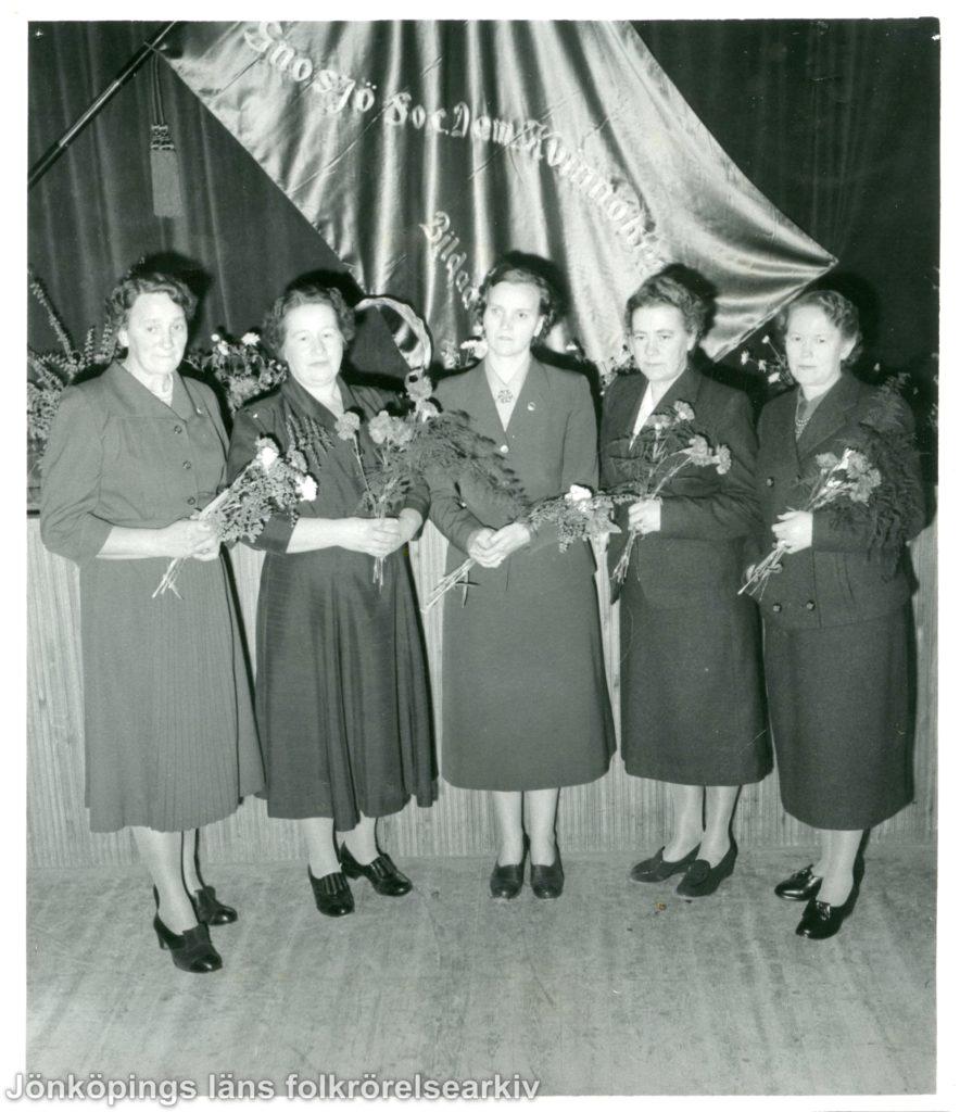 Fem kvinnor står med buketter i händerna framför en fana.