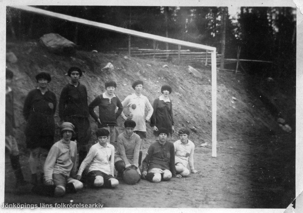 Ett tiotal kvinnor uppställda vid ett fotbollsmål. I bakgrunden en jordvall och längre bort en gärdesgård.