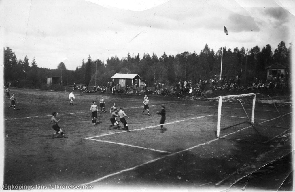 Foto taget snett ovan kortlinjen över fotbollsmatch. Längre bort syns spridd publik på bänkar och bergshällar.