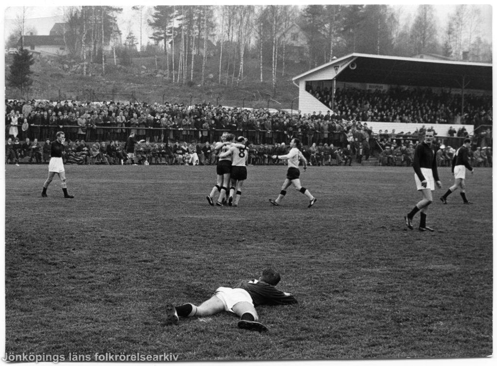 Fotbollsmatch. I förgrunden ligger en spelare i gräset. I bakgrunden syns en fullsatt läktare.