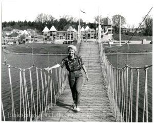 En kvinna går över en repbro över vatten. I bakgrunden lekställningar.