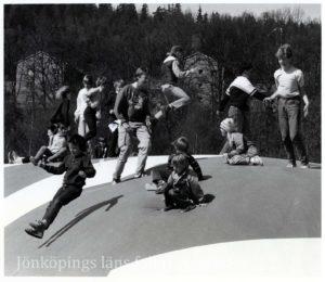 Ett tiotal ungdomar och barn hoppar på en stor hoppkudde.