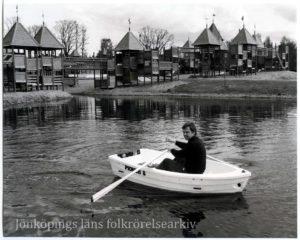 En man i roddbåt. I bakgrunden lekställningar.