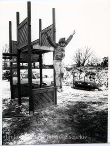 Ett barn hoppar ner från en lekställning.