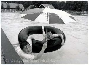 Två barn i en bassäng. De håller sig i en gummiring. Den ena har ett paraply i handen.