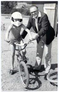 En man håller i en pojke på en BMX-cykel.