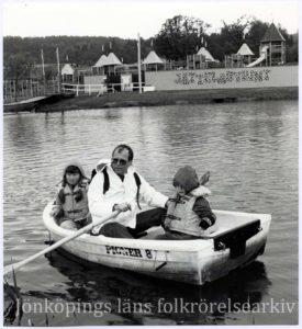En vuxen och två barn i en liten roddbåt. I bakgrunden klätterställningar.